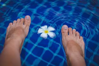 person-s-feet-on-swimming-pool-965988