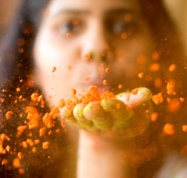 woman-blowing-orange-powder-3884596